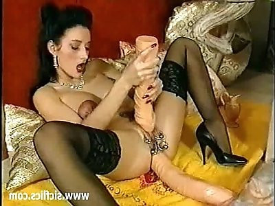 Busty brunette fucks her ass with a huge black dildo